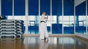Sporty kobieta w białym kimonie ćwiczy karate sztuczki w gym zbiory