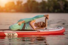 Sporty kobieta w joga pozyci na paddleboard, robi joga na sup desce, ćwiczeniu dla elastyczności i rozciągać, obraz royalty free