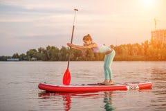 Sporty kobieta w joga pozyci na paddleboard, robi joga na sup desce, ćwiczeniu dla elastyczności i rozciągać, zdjęcia royalty free