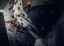 Sporty kobieta wspina się sztucznego głaz indoors obrazy royalty free