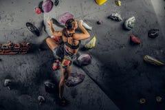Sporty kobieta wspina się sztucznego głaz indoors fotografia stock