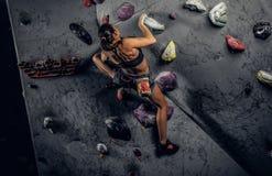 Sporty kobieta wspina się sztucznego głaz indoors obrazy stock
