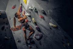 Sporty kobieta wspina się sztucznego głaz indoors obraz royalty free
