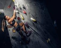 Sporty kobieta wspina się sztucznego głaz indoors zdjęcia stock