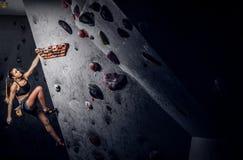 Sporty kobieta wspina się sztucznego głaz indoors fotografia royalty free