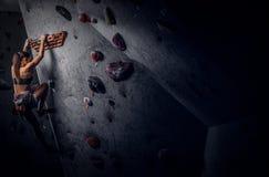 Sporty kobieta wspina się sztucznego głaz indoors zdjęcie stock