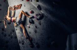 Sporty kobieta wspina się sztucznego głaz indoors obraz stock