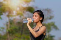 Sporty kobiety azjatykcia woda pitna plenerowa na słonecznym dniu obrazy royalty free