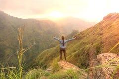 Sporty kobiety pozycja z nastroszonymi rękami na odgórnym wzgórzu patrzeje wschód słońca oh zdjęcie stock