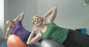Sporty kobiety robi gimnastycznym ćwiczeniom lub ćwiczy w sprawności fizycznej klasie zbiory wideo
