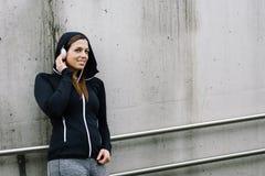 Sporty kobiety sÅ'uchajÄ…ca muzyka w ulicie zdjęcie stock
