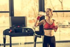 Sporty kobiety woda pitna od butelki podczas gdy stojący blisko trademill w gym Obrazy Royalty Free