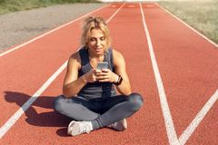 Sporty Lifestyle. Young woman on stadium sitting on track checking social media on smartphone smiling happy royalty free stock photos