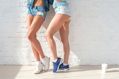 Sporty long sexy legs of two beautiful women jeans Stock Images