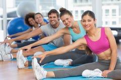 Sporty ludzie rozciąga ręki nogi w sprawności fizycznej studiu zdjęcia royalty free