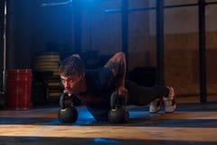Sporty mężczyzna podnosi z czajników dzwonami robić pcha Obrazy Royalty Free