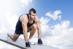 Sporty mężczyzna przygotowywa bieg przez nieba. zdjęcia stock