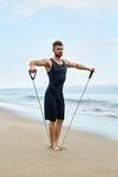 sporty Mężczyzna Robi Expander Ćwiczy Plenerowego Na plaży Ciało trening Zdjęcie Royalty Free
