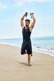 sporty Mężczyzna Robi Expander Ćwiczy Plenerowego Na plaży Ciało trening Obrazy Royalty Free