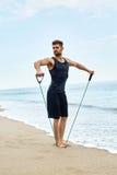 sporty Mężczyzna Robi Expander Ćwiczy Plenerowego Na plaży Ciało trening Zdjęcia Stock