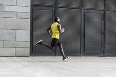 Sporty mężczyzna w żółtej koszulki działającym zmierzchu outdoors skacze Obraz Royalty Free