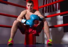 Sporty męski bokser siedzi blisko z nagą klatką piersiową w bokserskich rękawiczkach Fotografia Stock