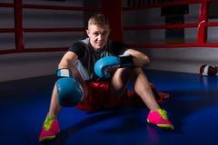 Sporty męski bokser siedzi w miarowym bokserskim Rin w bokserskich rękawiczkach Zdjęcia Stock