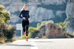 Sporty młoda kobieta bieg na halnej drodze w pięknej naturze fotografia royalty free