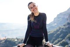 Sporty młoda kobieta patrzeje kamerę na halnym szczycie obrazy royalty free