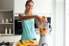 Sporty młoda kobieta robi jarzynowemu smoothie podczas gdy słuchający muzyka w jej kuchni fotografia royalty free