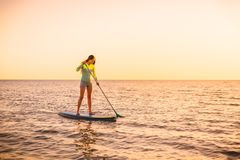 Sporty młoda kobieta stoi up paddle surfing z pięknymi zmierzchu lub wschodu słońca kolorami zdjęcia royalty free