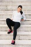 Sporty młoda kobieta texting na smartphone zdjęcia stock