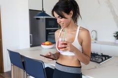 Sporty młoda kobieta używa jej telefon komórkowego w kuchni podczas gdy pijący truskawkowego smoothie w domu obrazy royalty free