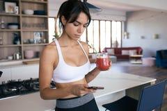 Sporty młoda kobieta używa jej telefon komórkowego w kuchni podczas gdy pijący truskawkowego smoothie w domu zdjęcie royalty free