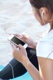 Sporty młoda kobieta używa telefon komórkowego Fotografia Royalty Free
