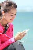 Sporty młoda kobieta używa telefon komórkowego Obrazy Stock