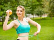 Sporty młoda kobieta z jabłczaną i pomiarową taśmą Obraz Royalty Free