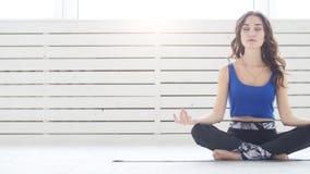Sporty młodej kobiety ćwiczy joga, siedzi w Przyrodnim Lotosowym ćwiczeniu, Siddhasana poza, salowy, domowy wewnętrzny tło, zbiory wideo