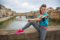 Sporty młodej kobiety obsiadanie i słuchający odtwarzacz mp3 Obraz Stock