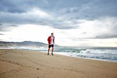 Sporty młody biegacz w sporta czerwonym windbreaker biega wzdłuż plaży na pięknym dennym tle Obraz Stock