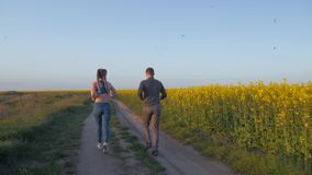 Sporty, młody sportowiec i kobieta z kanekalon warkoczy bieg wokoło outdoors, na naturze na okwitnięcie gwałta gazonie przeciw bł zdjęcie wideo