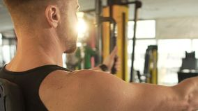 Sporty male with developed muscles doing chest fly exercise at fast pace in gym. Stock footage stock video footage