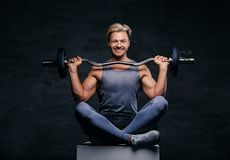 Sporty male is dressed in a grey sportswear holds barbel. Positive and smiling blond sporty male is dressed in a grey sportswear sits on a box and holds barbel royalty free stock photography