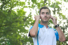 Sporty male runner adjusting his earphone during jogging Stock Photo