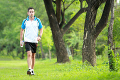 Sporty male runner walking by at roadside  while take a breath Stock Image