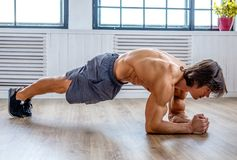 Sporty male standing on his elbows. Stomach workout Royalty Free Stock Images