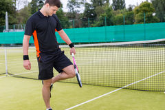 Sporty male tennis player warming up before tennis match. Sporty male tennis player wearing a sportswear warming up before tennis match on a court outdoor in Royalty Free Stock Photo