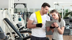 Sporty man ad woman using pc tablet at gym. stock video footage