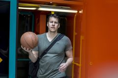 Sporty Man With a Basketball Walking out of a Subway Train. Athletic man with a basketball in hand walking out of a subway train in Frankfurt. Medium shot royalty free stock photography