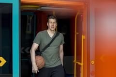 Sporty Man With a Basketball Walking out of a Subway Train. Athletic man with a basketball in hand walking out of a subway train in Frankfurt. Medium shot stock images